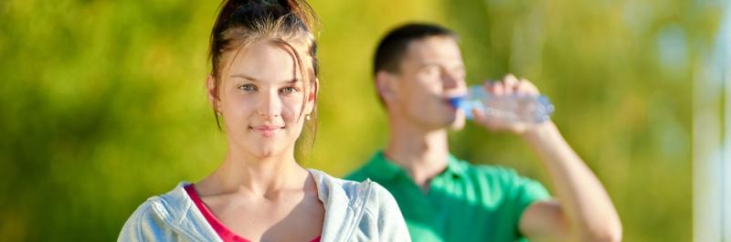 hoe verlies je gewicht, vrouw die flesje water in haar handen heeft