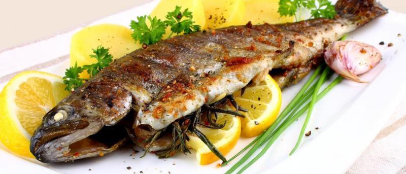 paleo dieet, vis op een bord met citroenen en uitjes