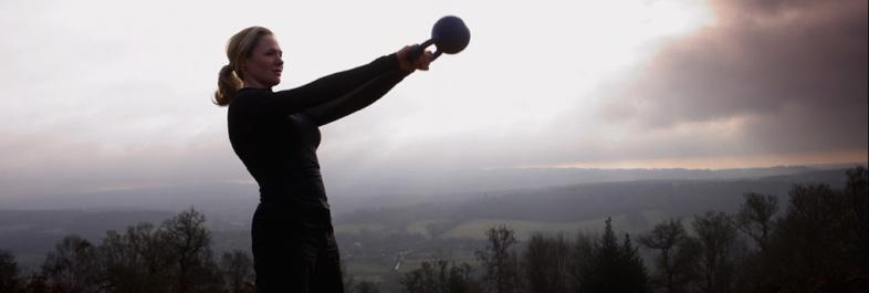 thuis een sixpack trainen met kettlebells, vrouw in natuur met kettlebell