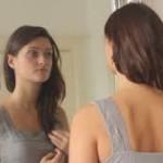Buikspieren trainen na bevalling, vrouw voor spiegel die buikspieren aanspant