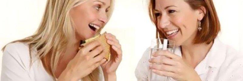 hoe verlies je gewicht, vrouw tijdens eten die een glaasje water drinkt
