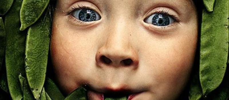 paleo dieet, kinjde met een groen boontje in zijn mond en rondom zijn gezichtje meer groene boontjes